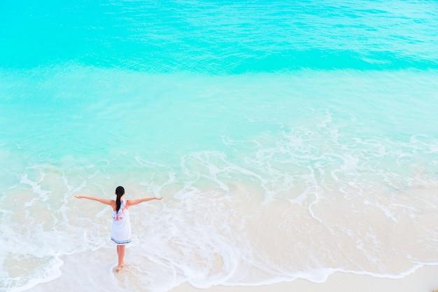 Junges glückliches touristisches mädchen am strand, der viel spaß im seichten wasser hat. draufsicht eines jungen mädchens und des schneeweißen strandes mit türkisfarbenem trinkwasser.
