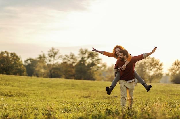 Junges glückliches verspieltes paar verliebt in huckepackfahrt. mann, der frau auf seinen rücken hält und auf einer wiese an einem schönen sonnigen herbsttag geht.