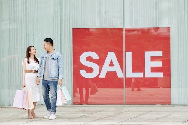 Junges glückliches vietnamesisches paar mit einkaufstüten, die am großen verkaufsbanner außerhalb des einkaufszentrums stehen