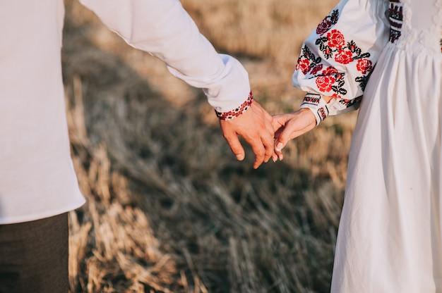 Junges händchenhalten des verheirateten paars, zeremoniehochzeitstag