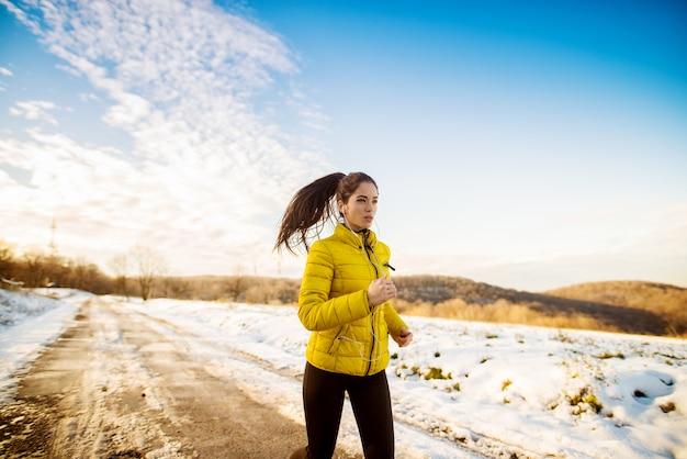 Junges hartnäckiges fitness-fokussiertes mädchen, das in der wintersportbekleidung draußen in der natur läuft.