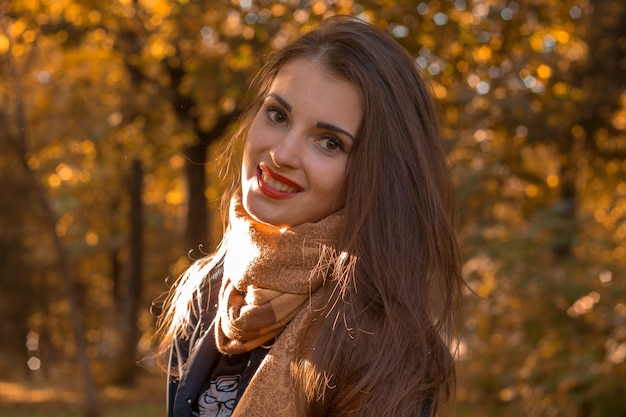 Junges heißes mädchen mit roten lippen steht im park freut sich und lächelt