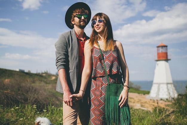 Junges hipsterpaar, das in der landschaft aufwirft