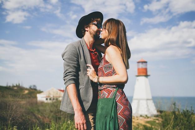 Junges hipsterpaar, das in der landschaft küsst