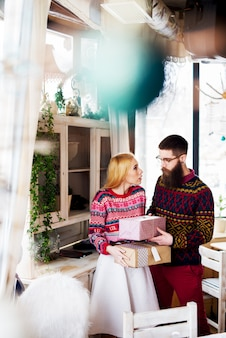 Junges hipsterpaar, das weihnachtsgeschenke einander gibt.