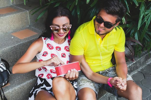 Junges hipsterpaar verliebt, musik auf lautsprecher hörend, glücklich lächelnd, spaß machend, sommeroutfit, tropischer urlaub, sonnenbrille