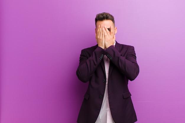 Junges hispanisches mannbedeckungsgesicht mit den händen, spähend zwischen finger mit überraschtem ausdruck und schauen zur seite
