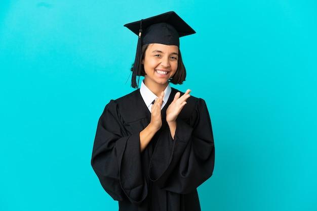 Junges hochschulabsolventenmädchen über isoliertem blauem hintergrund, das nach der präsentation in einer konferenz applaudiert