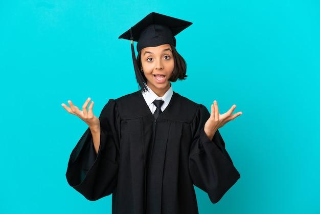 Junges hochschulabsolventenmädchen über isoliertem blauem hintergrund, das viel lächelt