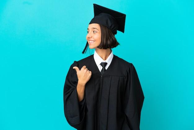 Junges hochschulabsolventenmädchen über isoliertem blauem hintergrund, der auf die seite zeigt, um ein produkt zu präsentieren