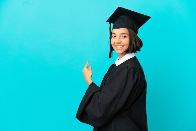 Junges hochschulabsolventenmädchen über isoliertem blauem hintergrund, der nach hinten zeigt