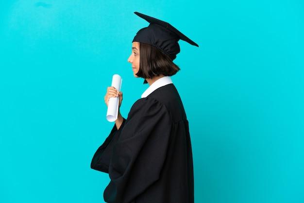 Junges hochschulabsolventenmädchen über isoliertem blauem hintergrund in seitlicher position