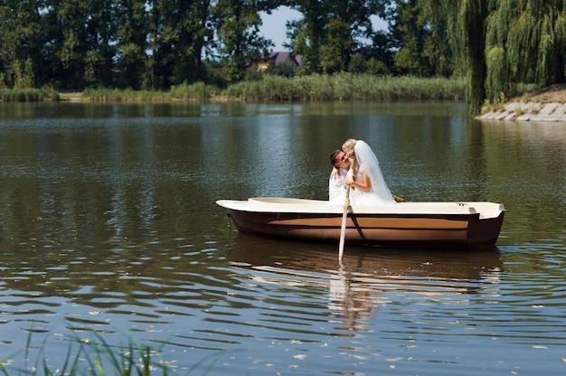 Junges hochzeitspaar, das auf dem boot segelt