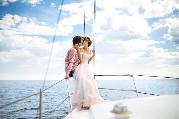 Junges hochzeitspaar, das romantische momente auf einer yacht auf see genießt.