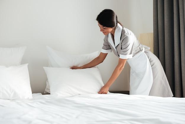 Junges hotelmädchen, das kissen auf bett aufstellt