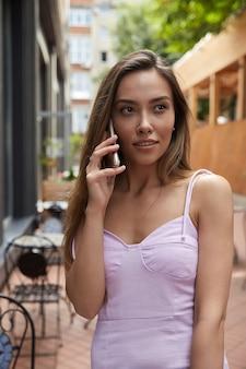 Junges hübsches asiatisches mädchen im rosafarbenen kleid, das draußen steht und mit dem smartphone anruft