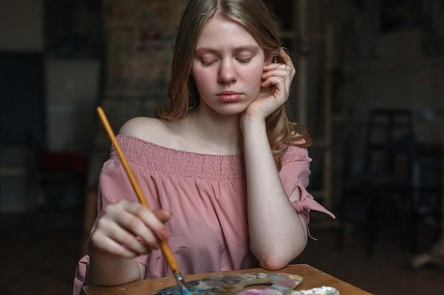 Junges hübsches blondes mädchen im rosafarbenen kleid steht ihren kopf auf ihrem arm still und mischt farben mit pinsel auf palette.