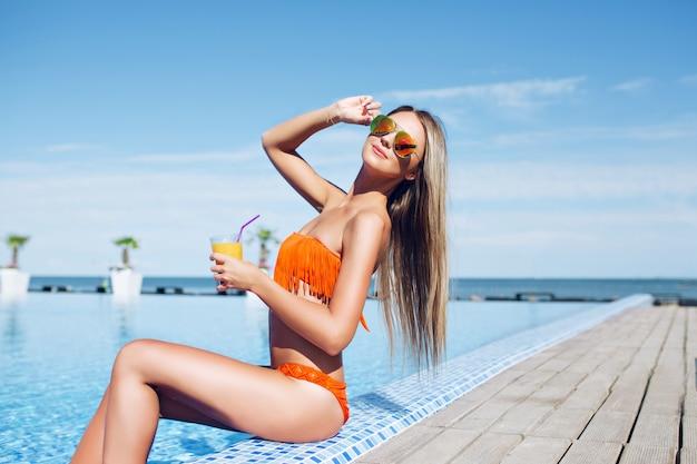 Junges hübsches blonf mädchen mit langen haaren sitzt nahe pool auf sonne. sie hält einen cocktail in der hand und lächelt in die kamera.