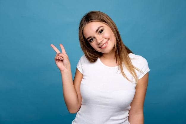 Junges hübsches brunettemädchen im weißen t-shirt, das finger auf v-zeichenart zeigt und, blauer hintergrund lächelt