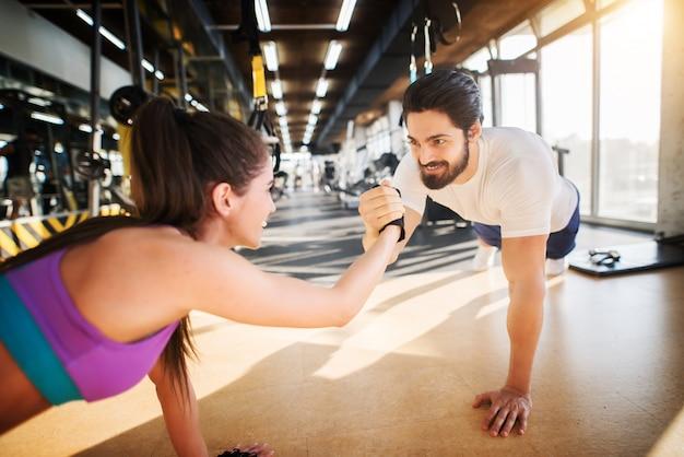 Junges hübsches fitnesspaar lächelt und hält sich an den händen, während sie liegestütze zusammen in der turnhalle machen.