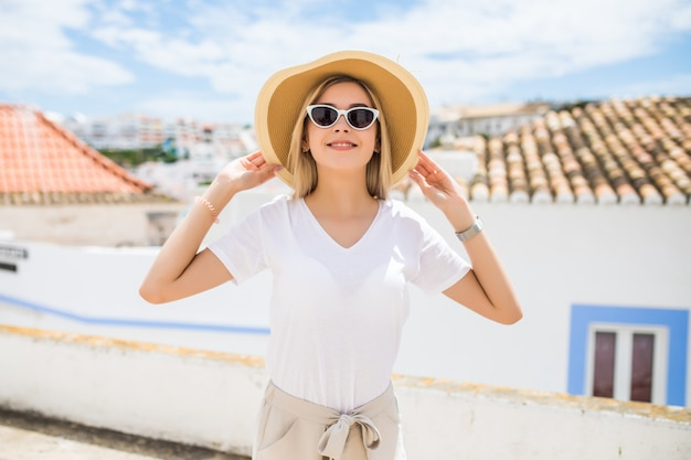 Junges hübsches hipster-fröhliches mädchen, das auf der straße am sonnigen tag aufwirft