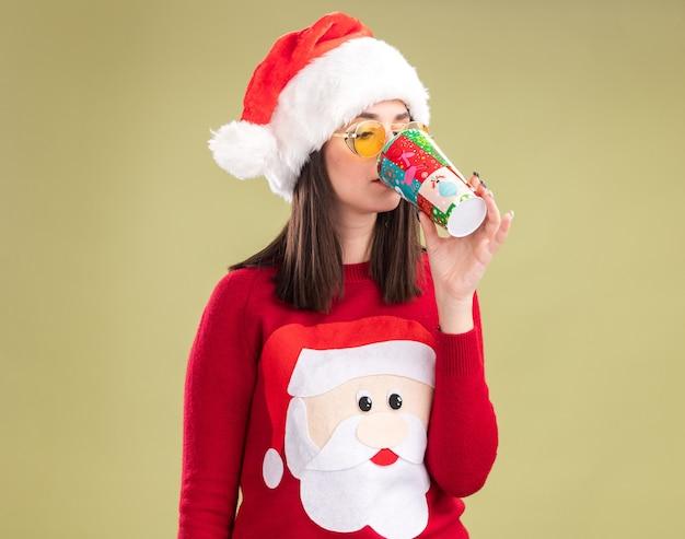 Junges hübsches kaukasisches mädchen mit weihnachtsmann-pullover und -hut mit brille, das kaffee aus plastikweihnachtsbecher trinkt, isoliert auf olivgrünem hintergrund