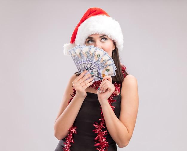 Junges hübsches kaukasisches mädchen mit weihnachtsmütze und lametta-girlande um den hals, das geld hält, das von hinten aufschaut, isoliert auf weißem hintergrund mit kopierraum