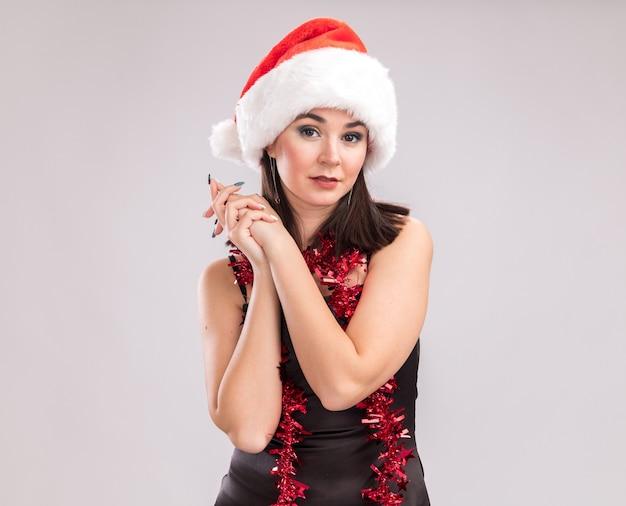 Junges hübsches kaukasisches mädchen mit weihnachtsmütze und lametta-girlande um den hals, das in die kamera schaut und die hände zusammenhält, isoliert auf weißem hintergrund mit kopierraum