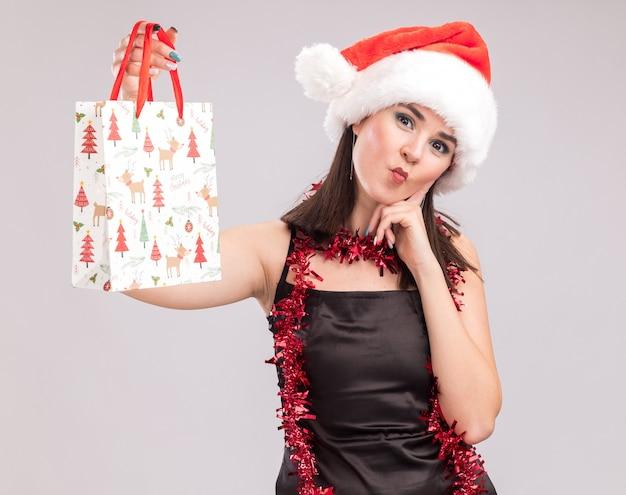 Junges hübsches kaukasisches mädchen mit weihnachtsmütze und lametta-girlande um den hals, das weihnachtsgeschenktüte hält und in die kamera schaut, die hand am kinn hält und fischgesicht isoliert auf weißem hintergrund macht