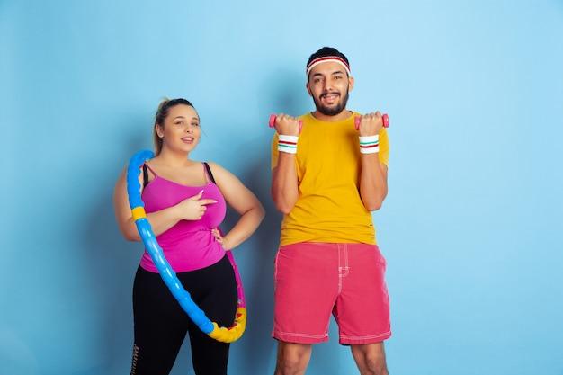Junges hübsches kaukasisches paar im hellen kleidertraining auf blauem hintergrund konzept des sports, der menschlichen gefühle, des ausdrucks, des gesunden lebensstils, der beziehung, der familie. üben mit reifen und gewichten.