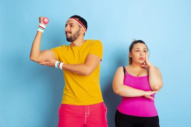 Junges hübsches kaukasisches paar im hellen kleidertraining auf blauem raum konzept des sports, der menschlichen gefühle, des ausdrucks, des gesunden lebensstils, der beziehung, der familie