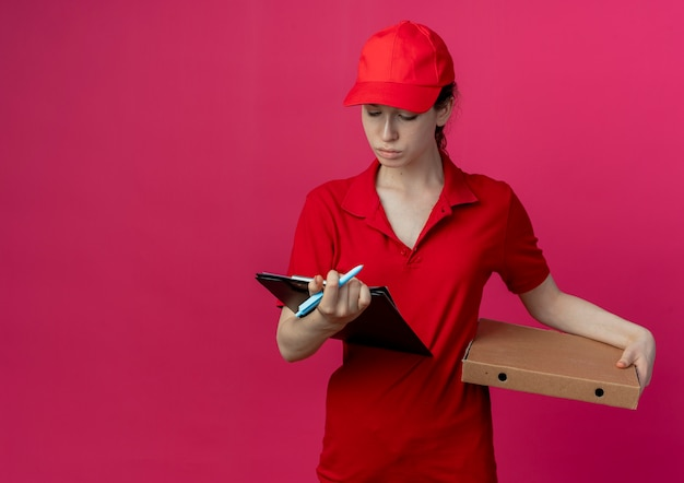 Junges hübsches liefermädchen in roter uniform und mütze, das pizzapaketstift und zwischenablage hält und auf die zwischenablage schaut