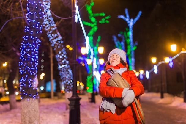 Junges hübsches lustiges mädchen, das im winter spaß im freien hat. weihnachts-, stadt- und winterferienkonzept.