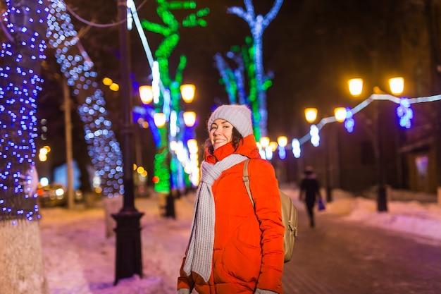 Junges hübsches lustiges mädchen, das spaß im freien im winterweihnachtsstadt- und winterferienkonzept hat