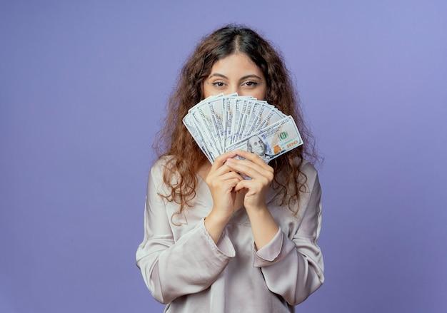 Junges hübsches mädchen bedeckt gesicht mit geld