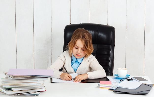 Junges hübsches mädchen, das am arbeitsplatz sitzt und im büro schreibt.