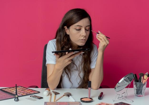 Junges hübsches mädchen, das am make-up-tisch mit make-up-werkzeugen hält, die lidschattenpalette betrachten spiegel betrachten und lidschatten mit einem geschlossenen auge lokalisiert auf purpurrotem hintergrund anwenden