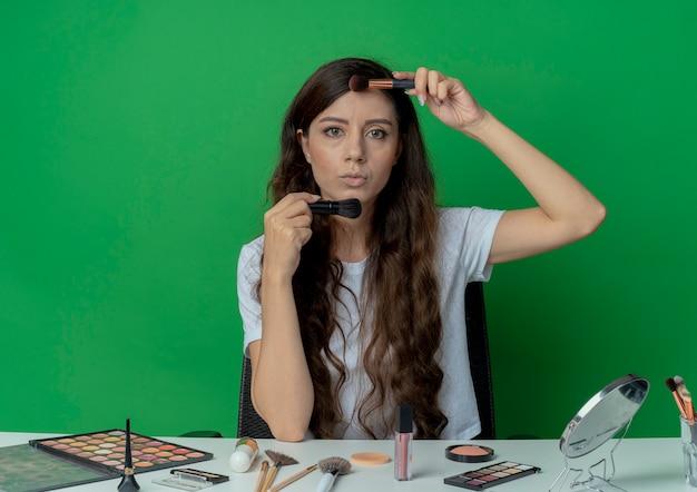 Junges hübsches mädchen, das am make-up-tisch mit make-up-werkzeugen hält, die make-up-bürsten nahe gesicht halten, das kamera lokalisiert auf grünem hintergrund betrachtet