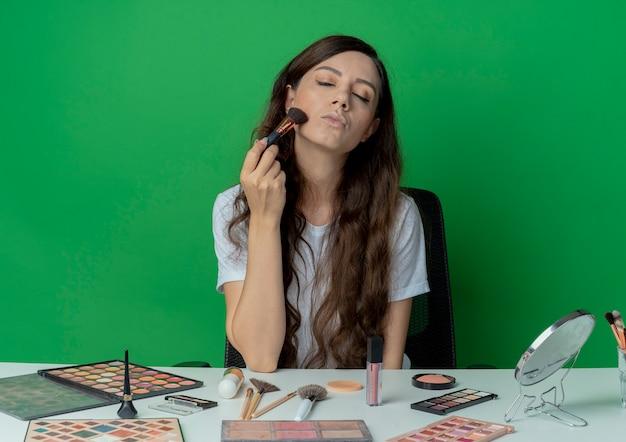 Junges hübsches mädchen, das am make-up-tisch mit make-up-werkzeugen sitzt, erröten auf wange mit pinsel mit geschlossenen augen lokalisiert auf grünem hintergrund