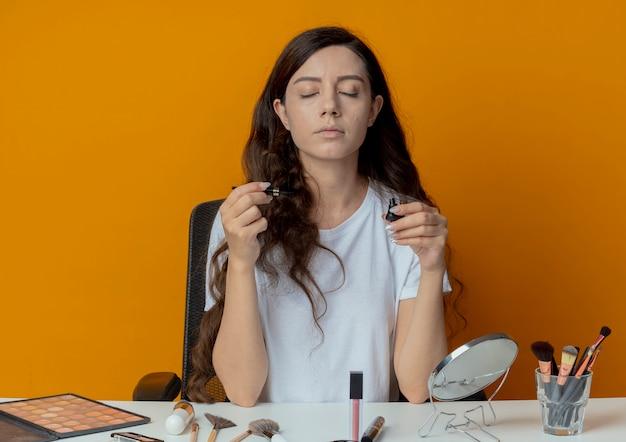 Junges hübsches mädchen, das am make-up-tisch mit make-up-werkzeugen sitzt, hält eyeliner mit geschlossenen augen lokalisiert auf orange hintergrund