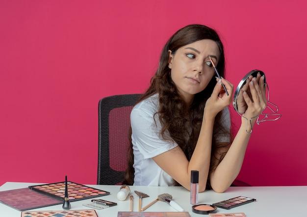 Junges hübsches mädchen, das am make-up-tisch mit make-up-werkzeugen sitzt und den spiegel betrachtet, der ihre augenbraue mit make-up-pinsel lokalisiert auf purpurrotem hintergrund formt