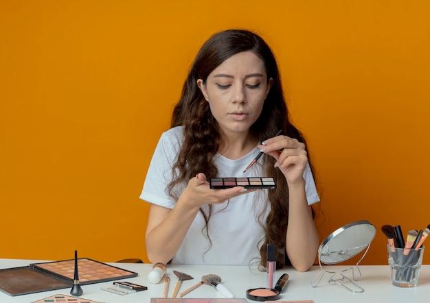 Junges hübsches mädchen, das am make-up-tisch mit make-up-werkzeugen sitzt und lidschattenpalette hält und lidschattenpinsel lokalisiert auf orangefarbenem hintergrund hält