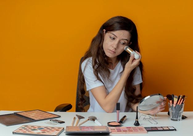 Junges hübsches mädchen, das am make-up-tisch mit make-up-werkzeugen sitzt und spiegel betrachtet und fundament mit pinsel lokalisiert auf orange hintergrund hält