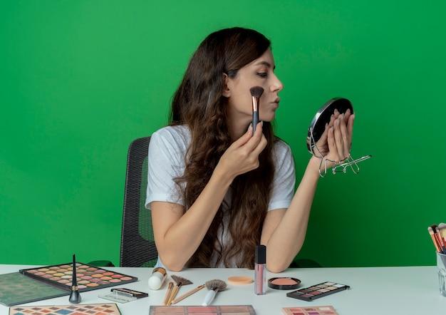 Junges hübsches mädchen, das am make-up-tisch mit make-up-werkzeugen sitzt und spiegel betrachtet und pulver mit pinsel lokalisiert auf grünem hintergrund betrachtet
