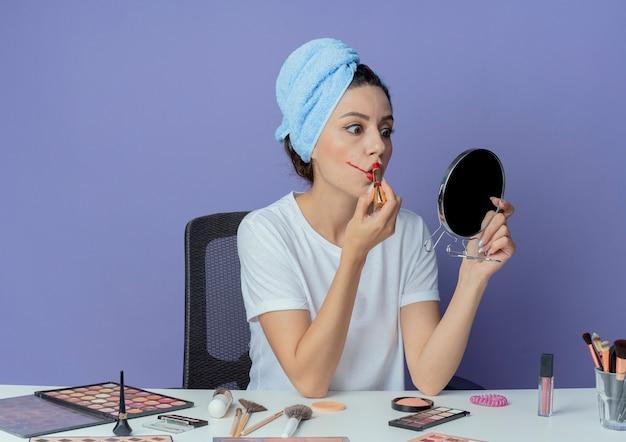 Junges hübsches mädchen, das am make-up-tisch mit make-up-werkzeugen und mit badetuch auf kopf hält spiegel hält und auf roten lippenstift lokalisiert auf lila hintergrund setzt