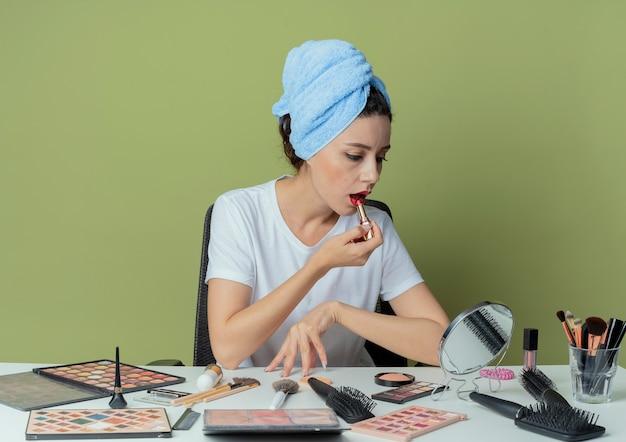 Junges hübsches mädchen, das am schminktisch mit schminkwerkzeugen und mit handtuch auf dem kopf sitzt, den spiegel betrachtet und roten lippenstift aufsetzt und den tisch auf olivgrünem grün berührt?