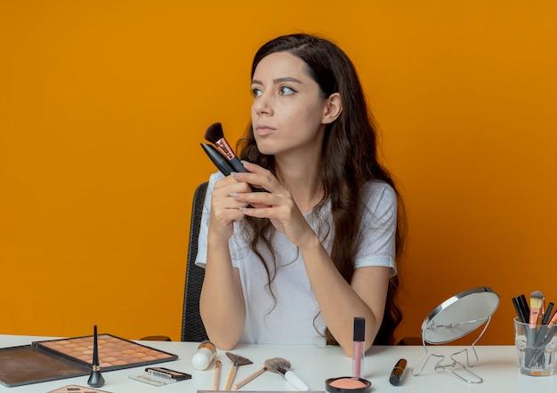 Junges hübsches mädchen, das an make-up-tabelle mit make-up-werkzeugen hält, die puderpinsel und wimperntusche halten und seite lokalisiert auf orange hintergrund betrachten
