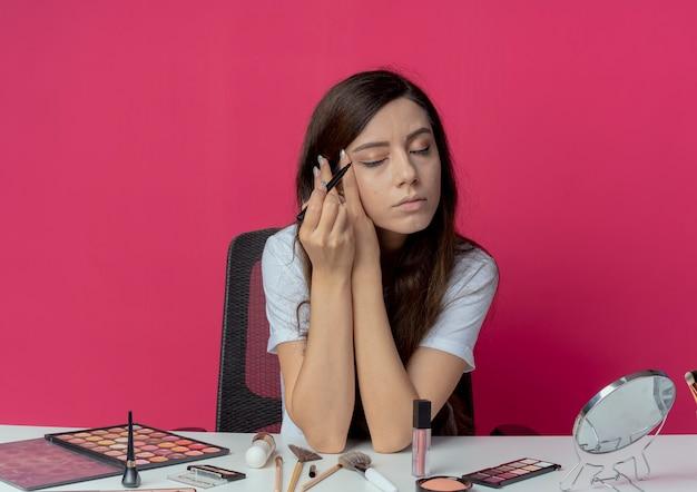 Junges hübsches mädchen, das an make-up-tabelle mit make-up-werkzeugen sitzt, die eyeliner anwenden und gesicht mit geschlossenen augen lokalisiert auf purpurrotem hintergrund berühren