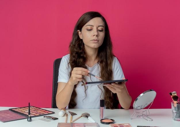 Junges hübsches mädchen, das an make-up-tabelle mit make-up-werkzeugen sitzt, die lidschatten-palette und pinsel halten und palette lokalisiert auf purpurrotem hintergrund betrachten