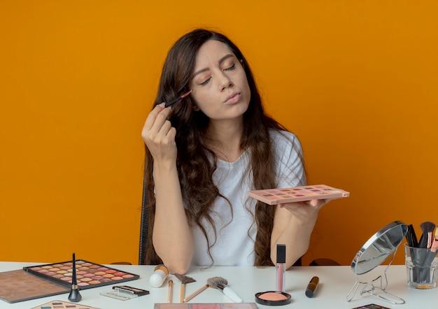 Junges hübsches mädchen, das an make-up-tabelle mit make-up-werkzeugen sitzt, die schattenpalette halten und lidschatten mit pinsel mit geschlossenen augen lokalisiert auf orange hintergrund anwenden
